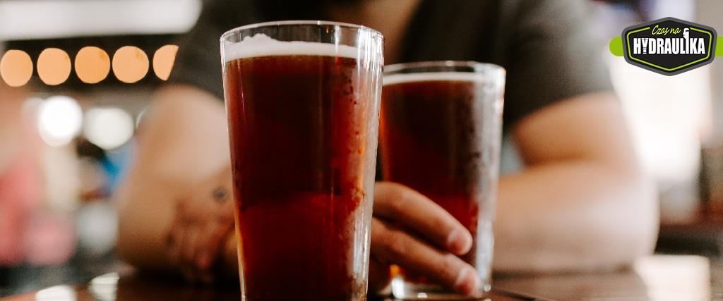 Dwa kufle z piwem stojące na stole, po jeden z nich sięga człowiek, którego sylwetkę widać w tle