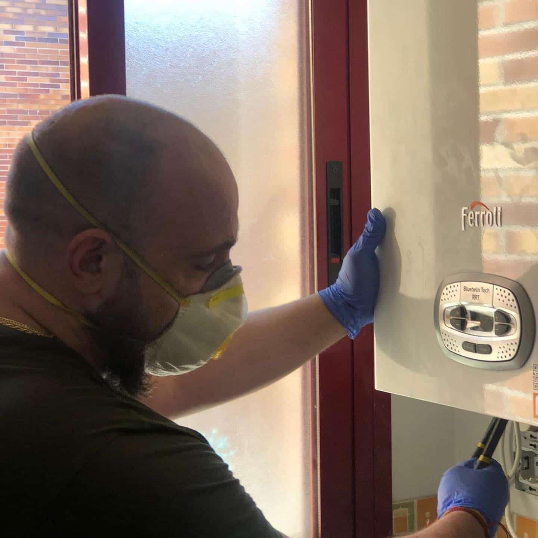 człowiek w masce i rękawiczkach naprawia urządzenie grzewcze na tle okna